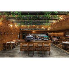 """O restaurante mexicano """"50 Friends Interlomas"""" conta com plantas no pergolado de madeira. O estilo contemporâneo do ambiente da foto valoriza a presença de materiais naturais na decoração. Projeto intimista do escritório Braverman Arquitectos. #arquitetura #design #decoração"""