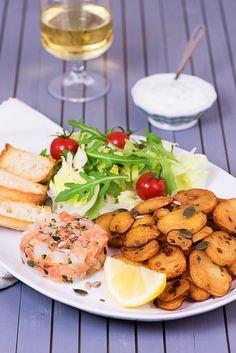 Tartare de Saumon et Gabillaud : Tartare de saumon et cabillaud finement citronné, pommes de terre sautées, salade, sauce fines herbes, tomates cerises, petits pains grillés aux herbes et huile d'olive, graines.