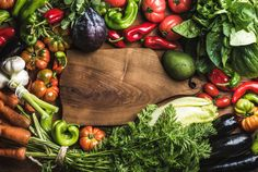 #Fresh raw vegetable ingredients  Fresh raw vegetable ingredients for healthy cooking or salad making with rustic wood board in center top view copy space horizontal composition. Diet or vegetarian food concept