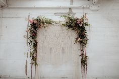 Intricate macramé hanging with pink + sage floral garland is a simple and sweet ceremony backdrop | Image by Chasewild