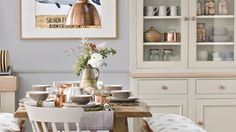 Hints of copper in this grey country dining room add a contemporary feel to the space