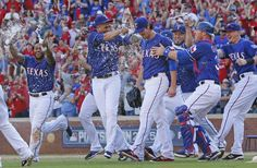 Texas Rangers starting pitcher Cole Hamels (35) is mobbed by teammates after pitching a complete game to clinch the Western Division with a 9-2 victory during the Los Angeles Angels vs. the Texas Rangers major league baseball game at Globe Life Park in Arlington on Sunday, October 4, 2015. (Louis DeLuca/The Dallas Morning News)
