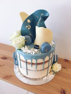 Baby shower cake in white baked buttercream with blue drip, chocolate shards, macarons, white blooms & gold leaf specks #haranspatisserie