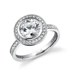 This dazzling 18K white gold engagement ring features a 1 carat round brilliant center diamond. Accentuated by surrounding diamonds and diamonds continuing down the sides of the ring totaling 0.48 carats. This diamond engagement ring is available in any shape or size center diamond, in 18K white gold or platinum. All Sylvie Collection diamond engagement rings are available with a flush fit matching wedding band. (For pricing on this diamond engagement ring and other diamond engagement rings…