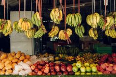 Bananas hanging and a lot of tropical fruits in a market shop by Jordi Rulló for Stocksy United