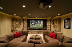 Basement media room/family room. Large dark brown sectional sofa, large screen wall mounted TV and stacked stone.