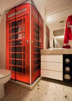 Projetado pela arquiteta Juliana Pippi, o banheiro de 3,5 m² segue o mesmo tema do estúdio. O box possui plotagem translúcida que remete à cabine telefônica de Londres, cidade de origem das bandas preferidas do morador. O tom sóbrio do piso, das louças e dos móveis contrastam com a cor forte do box e deixam o ambiente harmônico.