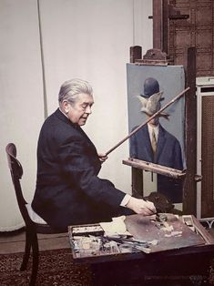 René Magritte at work in his living room, 1964.