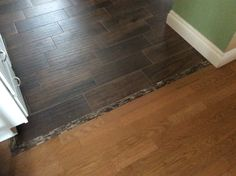 Our completed kitchen floor.  Removed the oak engineered hardwood (same as seen here) and replaced with wood look-alike ceramic tile. Used a mosaic for the transition.  No elevation change so iRobot just rolls right into the room.