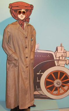 """Automobile Duster and Goggles, 1900-09  Linen with oilcloth trim. Goggles, leather with cotton binding; metal eyepieces with tinted glass; replacement ties. In the early years of the automobile, driving was as much a sport as it was transportation. Open cars required protective outerwear—a """"duster"""" coat the color of the dust and mud sure to cling to the driver, goggles, and for ladies, hats firmly kept in place with long veils which kept dust off the face."""