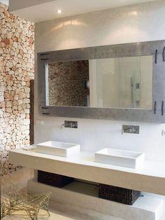 reforma baño en vivienda rehabilitada con lavabos sobre mueble de obra acabado microcemento, zona de ducha elevada.