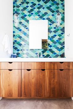 Ocean-inspired tiles in white bathroom with light wood cabinetry