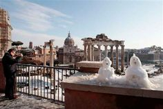 A man takes a picture of the snow covered Roman Forum in Rome. After no big snowfall for 26 years, Rome was hit by its second snowstorm in a week. (AP Photo/Gregorio Borgia)