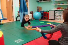 A child in prone on a platform swing reaching for an object in front of him improves balance as well as increases head and neck control. In this case, the child may be pulling himself, which would also improve upper extremity strength and grip strength.