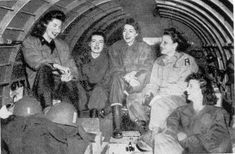 Photograph showing five members of the Nursing staff of the 96th Evacuation Hospital in flight with equipment necessary to establish the Hospital upon landing; final destination is Gießen, Germany. Picture taken 30 March 1945.