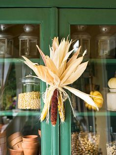 Tie a grouping of Indian corn ears together and hang from a cabinet door. Display jars filled with dried corn and seeds behind glass-front cabinet doors.