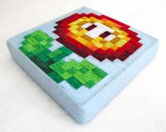 Super Mario Bros. fire flower made from squares of felt on canvas