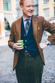 Drake's Diary - Staff Style. Our Creative Director, MH, grabbing a quick caffeine boost round the corner from No.3 Haberdasher Street. Wearing a few pieces from our AW15 Collection including Tweed Jacket, Slim Fit Essential Shirt, 36oz Foulard Silk Tie, Cashmere Sleeveless Cardigan, Wool and Silk Pocket Square and Bridle Belt.