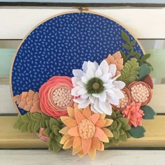 9 embroidery hoop with blue fabric and lots of handmade felt flowers and leaves in coral, peach and white.
