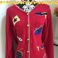 ✳️Listing✳️Beautiful Red Sweater ✳️Listing✳️Beautiful Embellished Susan Graver Cardigan Sweater in a Rich Lipstick Red with Gold trim around the collar and down the front. The satiny appliqués are all shoes and bags!!! With tiny gold pearls throughout. Gently loved. The only area I could find with 2 tiny pulls. Susan Graver Sweaters Cardigans