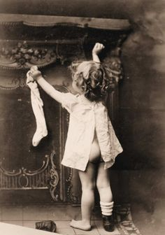 A little child hanging her sock for Santa Claus. Christmas in the making, XIX century.