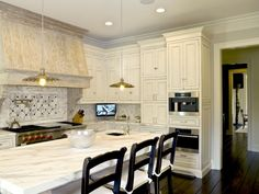 Amazing kitchen with antique white kitchen cabinets paired with white marble countertops and marble tiled backsplash.