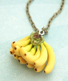 this necklace features a handmade banana bunch pendant made from polymer clay. it measures 1.5' x 1 ' and hangs from a bronze chain necklace that measures 24 inches in length. SKU:1022