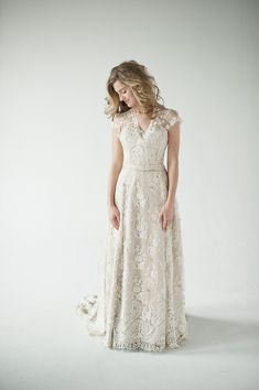 Ginny: Thousands of hand applied swarovski crystals and hand made tiny silk flowers cover the bottom of this silk charmeuse and French lace gown.