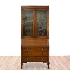 This antique secretary desk is featured in a solid quarter sawn oak wood with a glossy finish. This traditional style drop front desk has a hutch top with glass panel doors, 3 spacious drawers with dovetailed joinery, and cabriole legs. Perfect for showing off fine china and storing silverware! #americantraditional #desks #secretarydesk #sandiegovintage #vintagefurniture