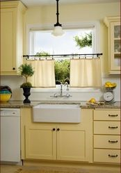 Sunny Yellow Kitchen: This charming kitchen in a 1927 Portland house - sunny yellow paint. Check out the extra-deep drawers, the Marmoleum tiles laid on the diagonal, the farmhouse sink, and the lighting from Schoolhouse Electric. Pale Yellow Kitchens, Yellow Kitchen Walls, Yellow Cabinets, Yellow Kitchen Designs, Turquoise Cabinets, Kitchen White, Dark Cabinets, New Kitchen, Vintage Kitchen