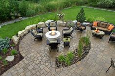 Another fire pit patio – gas-burning Basalt-column water feature Easy access for guests from the driveway Night lighting Solve some drainage issues Natural stone boulders around the fire pit are Fond du Lac limestone. The same limestone is used as bed edging. Patio and sidewalk pavers are Belgard Urbana. Permeable pavers in the driveway are a solution to hardcover issues. Uplighting on trees and along the sidewalk draw friends into the back yard.