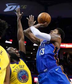 Oklahoma City Thunder forward Paul George (13) shoots as Golden State Warriors forward Draymond Green (23) defends during the second half of an NBA basketball game in Oklahoma City, Tuesday, April 3, 2018. (AP Photo/Sue Ogrocki)