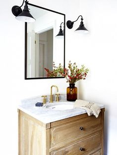 White bathroom with industrial wall sconces, black mirror, and brown vase for flowers