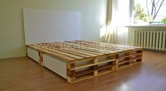A simple and elegant lacquered pallet platform bed with rolling storage underneath.