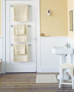 Few bathrooms have enough places to hang towels. Stacking towel bars behind closed doors is a great way to remedy the shortage and use space efficiently. A flat or single-paneled door provides a crisp frame for three bars; furthermore, it's easier to affix them to a wooden door (as most are) than to a wallboard or a plaster wall. Hang the hardware according to package instructions, evenly spacing the bars along the length of the door.