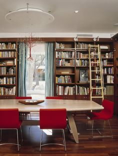 McKinney York Architects SaveEmail A wall of built-in bookshelves designed by McKinney York Architects graces this contemporary dining room in Austin, Texas. A library ladder on wheels allows the homeowners to easily reach books on the top shelves. The room's sculptural chandelier was created by local artists.