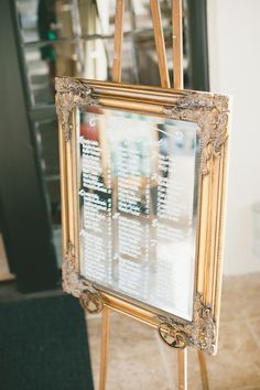 One of a set of two gold framed custom mirror seating charts. Hand painted.