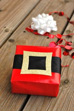 Santa Wrap: Shiny red wrapping paper Black ribbon (1/2- to 1-inch thick) Square glittery gold card stock with the center cut out