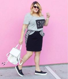 A grey tee tucked into a black pencil skirt is accessorized with a white leather backpack and black slip-on sneakers.