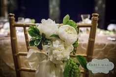 White peonies, waxy green leaves, and satin ribbon dress up a gold chair at a wedding reception in the elegant Carnegie Music Hall Foyer, Pittsburgh. The event featured gorgeous gold table cloths and floral arrangements from Gidas Flowers, a local flower shop owned by the bride's family. The John Parker Band had the honor of performing for the newlyweds and their guests at the reception. http://www.jpband.com/weddings/