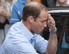 Prince William jokingly wipes sweat from his brow as he puts his new son into the car seat for the first time.