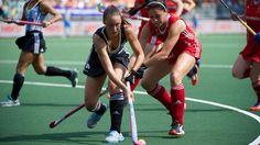 Este es un juego de críquet femenino de la Argentina . Las mujeres están usando uniformes de color rojo y azul para competir.
