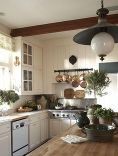 Off-white walls, warm wood tones, black/ORB decorative elements, eye-catching light fixture, greenery