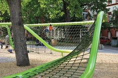 To create an undulating climbing space that meanders through the trees, designers erected two green steel pipes with a net strung between. In some sections, traversing the structure can involve swinging from ropes with rotating plates.