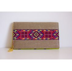 #Designed and handcrafted by Yasmoon# Clutch with a strip of Palestinian handmade embroidery on the front side and a gold chain#Back side made of fabric rich in bright colours and linear design#Colors of embroidery:Magenta, fucia, blue, green, yellow and purple# Size:20cm x 32cm# www.ananasa.com