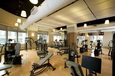 """We suggested a design to create a warm and comfortable fitness experience. By adding a new vinyl """"wood look flooring"""" (easy maintenance), keep the existing black painted ceiling and use it as a backdrop to graphic suspended panel ceiling, add decorative lighting and some glass tiles. We gave this facility a completely new look and feel. And there clients love it !!"""