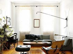 Masculine living room with piano, articulated sconce, long linen drapes, and leather Eames lounge chair.