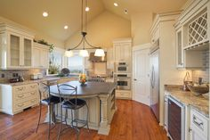 Bight and open kitchen with glass faced cabinets and large island.