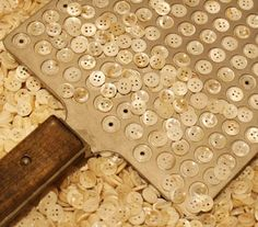 (::) Mother-of-Pearl Buttons. You can count out a gross (144 buttons) with a specially indented wooden paddle. Click for an interesting story about button manufacturing in Muscatine, Iowa where shells from the banks of the Mississippi were harvested to make these buttons.