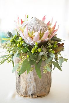 A protea centerpiece with gum leaf texture is an exotic alternative to more traditional flowers.